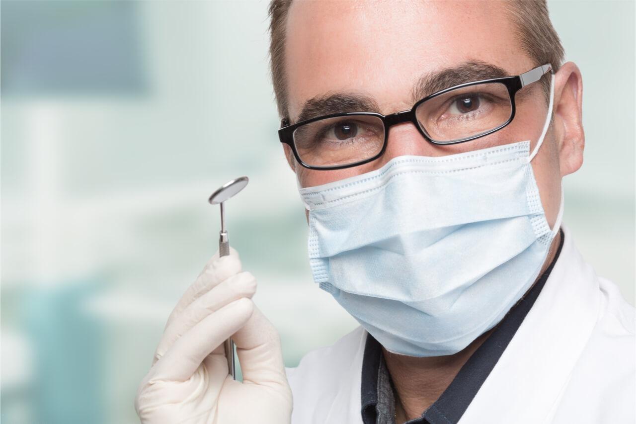 a dentist holding a dental equipment