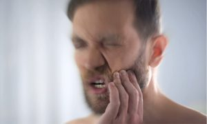 A man experiencing severe pain from a toothache.